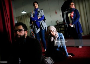 LOMALINDA-ME-December 6, 2015 -  Najoa Bouzidi (center sitting down) listens to speakers during a memorial service Dec. 06, 15, at the Islamic Community Center of Redlands in Loma Linda to remember the victims of  the San Bernardino rampage. Local churches and faith communities were in attendance to show a united front. (Barbara Davidson/The Los Angeles Times)