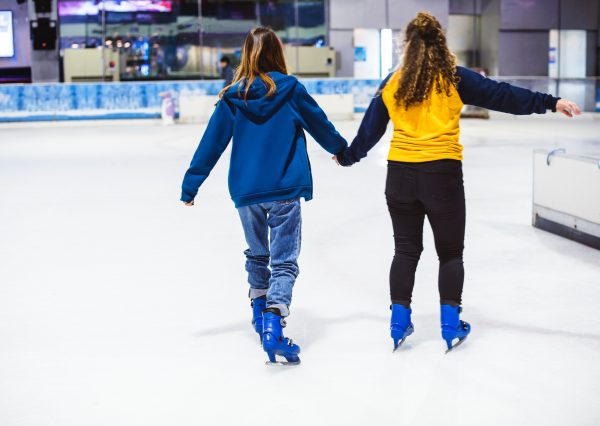 Exercise As Social Activity: two friends holding hands ice skating