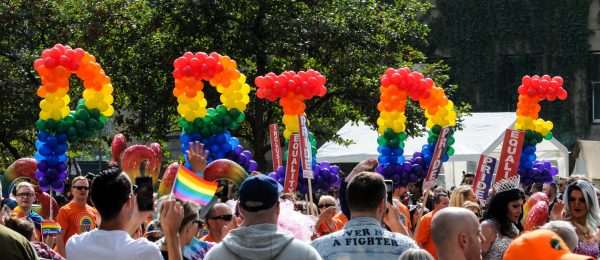 people at a parade hold balloons that spell out 'pride'