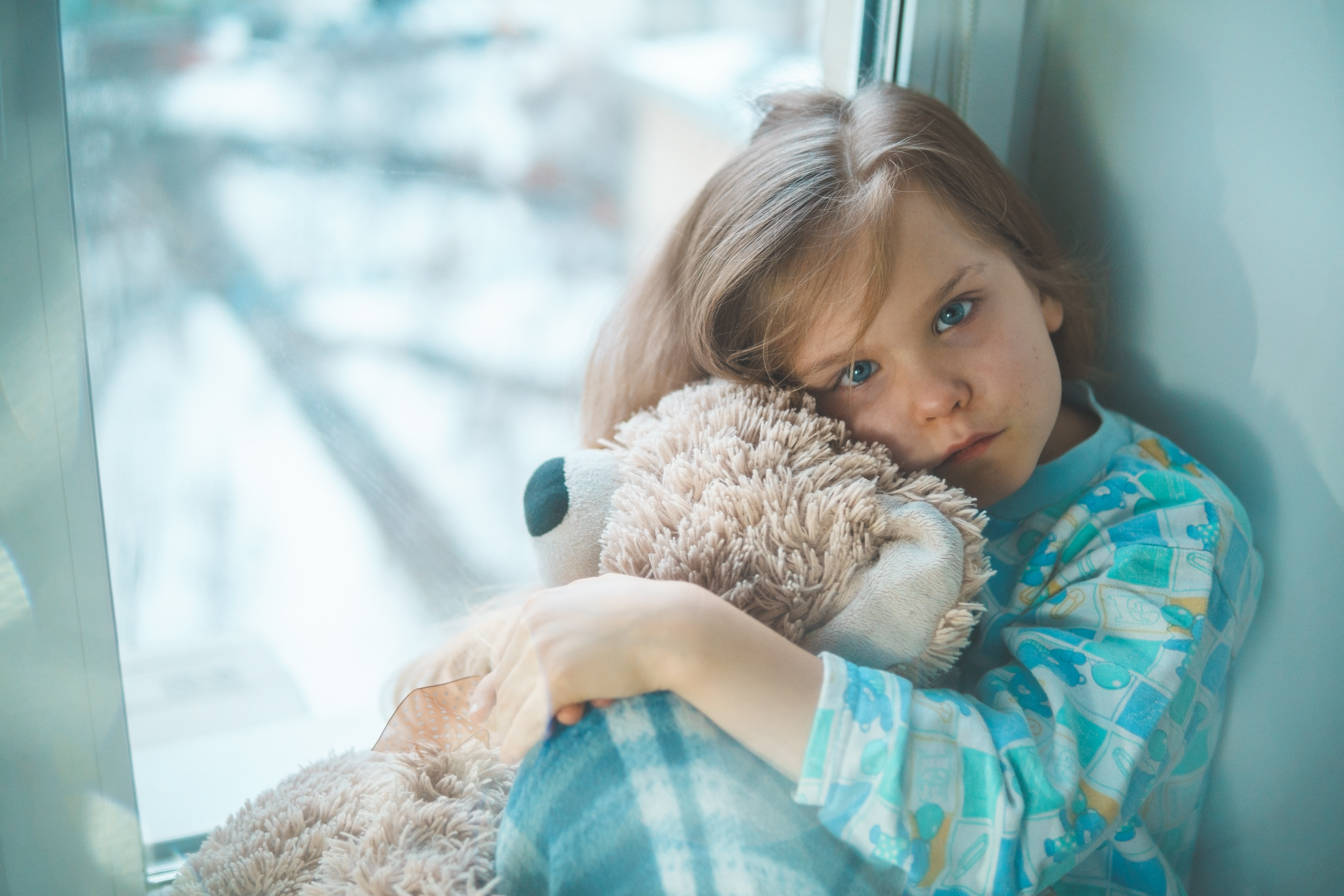 a sick child with a fever sitting at home